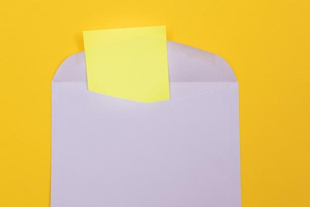 Fioletowa koperta z pustą żółtą kartką papieru w środku