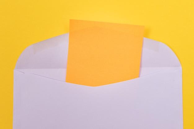 Fioletowa koperta z pustym pomarańczowym arkuszem papieru w środku