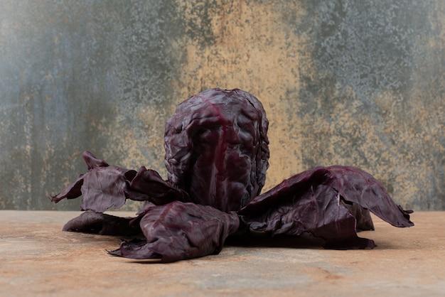 Fioletowa świeża kapusta na marmurze.
