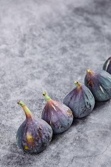 Fioletowe dojrzałe figi na marmurze.