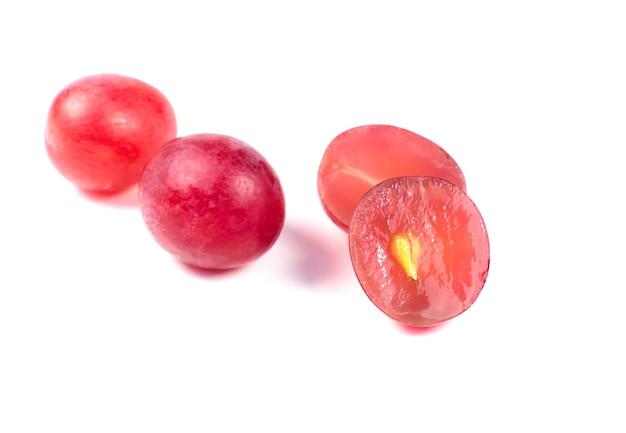 Fioletowe dojrzałe winogrona przeciąć na pół na białym tle. zamknij się zdjęcie. ekologiczne owoce dla wegan. witaminy.
