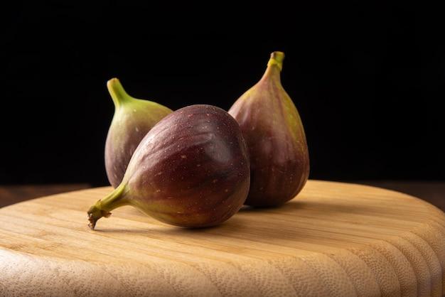 Fioletowe figi, fioletowe figi w drewnianym naczyniu na rustykalnym drewnie
