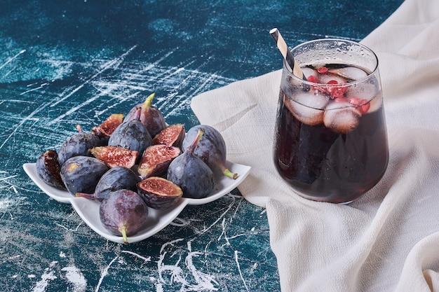 Fioletowe figi i kubek napoju na niebiesko.