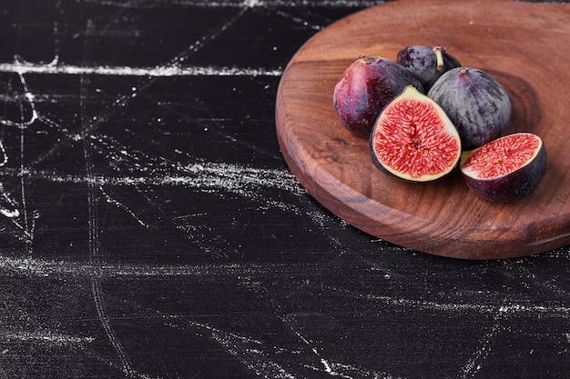 Fioletowe figi na drewnianym talerzu.