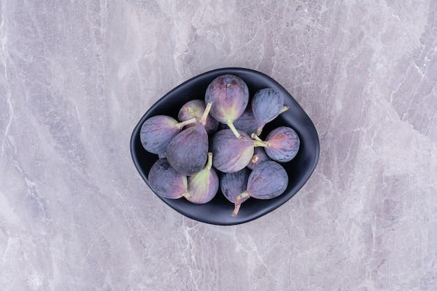 Fioletowe figi w czarnej ceramicznej misce, widok z góry.