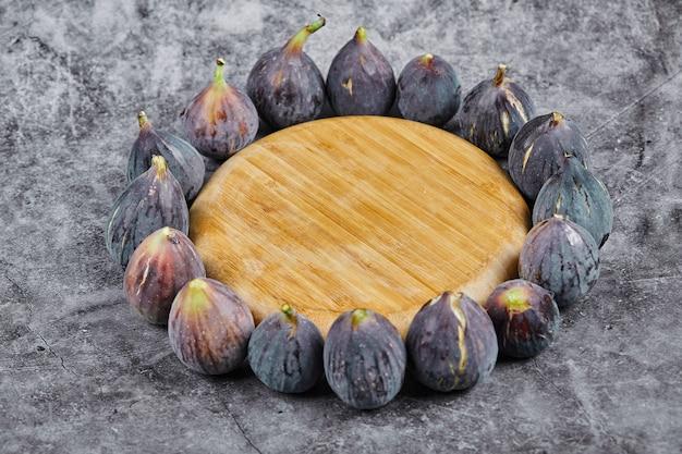 Fioletowe figi wokół drewnianego talerza na marmurze.