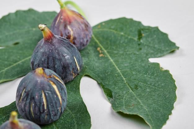 Fioletowe figi z liściem na białym tle.