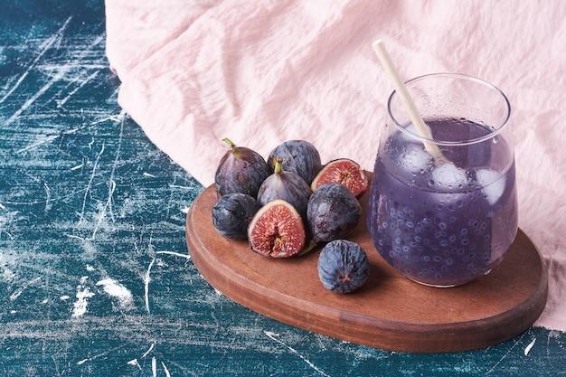 Fioletowe figi ze szklanką soku na niebiesko.