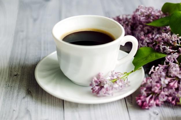 Fioletowe gałęzie kwiatu bzu e i filiżanka kawy