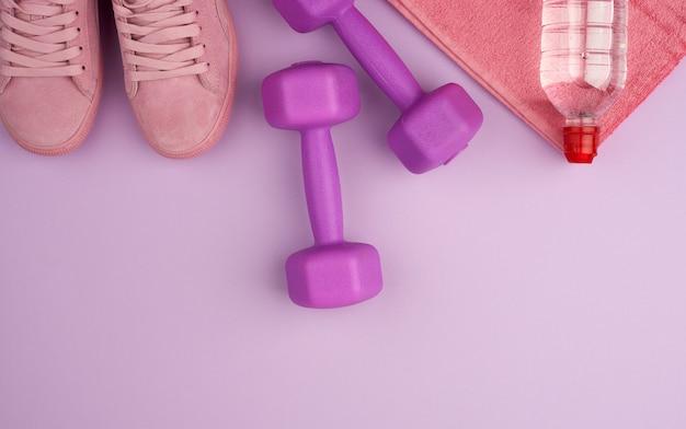 Fioletowe hantle i przezroczysta plastikowa butelka wody, różowy but na ręcznik frotte, widok z góry, leżał płasko