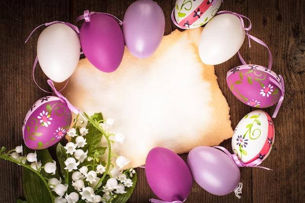 Fioletowe i białe jajka i pusta kartka z życzeniami. dekoracje wielkanocne