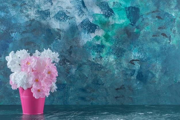 Fioletowe i białe kwiaty w różowym wiaderku, na białym tle.