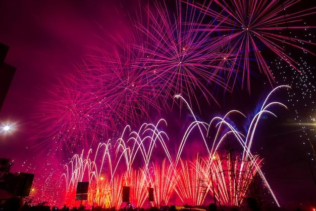 Fioletowe i czerwone świąteczne fajerwerki. międzynarodowy festiwal fajerwerków rostec