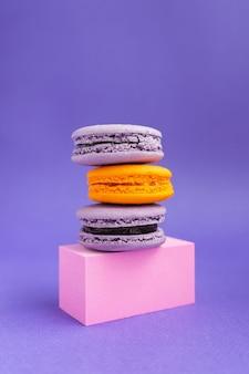 Fioletowe i pomarańczowe makaroniki na cokole. francuski deser na halloween. wypieki z mąki migdałowej.