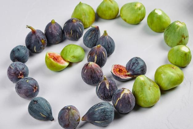 Fioletowe i zielone figi na białym tle.