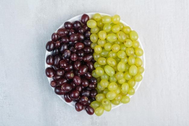 Fioletowe i zielone winogrona na białym talerzu. zdjęcie wysokiej jakości