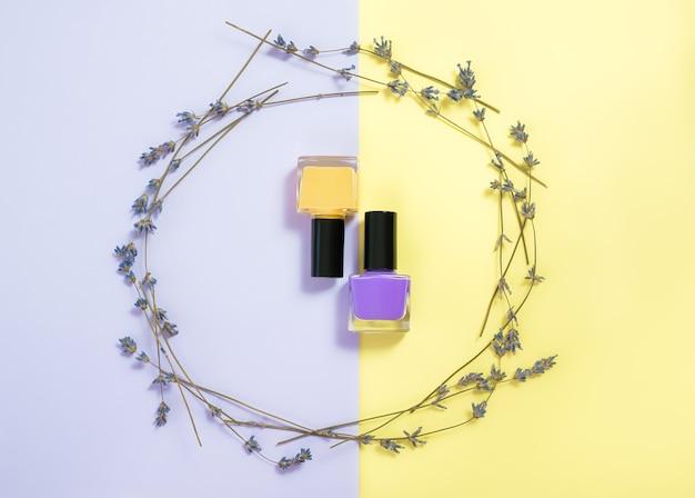 Fioletowe i żółte lakiery do paznokci na fioletowo-żółtej powierzchni.