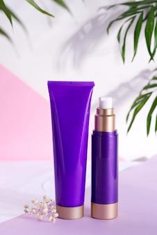 Fioletowe kosmetyczne plastikowe butelki na krem i balsam z zielonymi liśćmi ziołowymi i kwiatami na trójkolorowym tle.