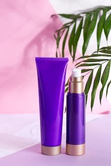 Fioletowe kosmetyczne plastikowe butelki na krem i balsam z zielonymi liśćmi ziołowymi i kwiatami na trójkolorowym