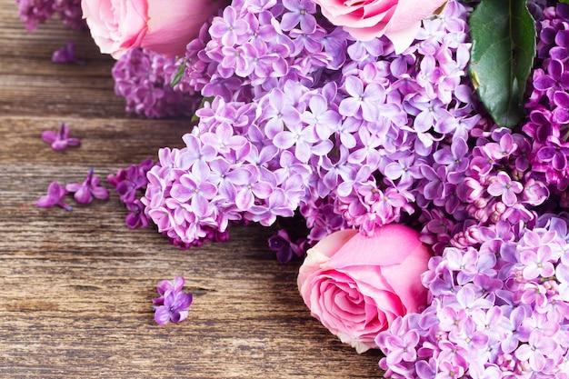 Fioletowe kwiaty bzu z różowe róże z bliska na drewnianym stole