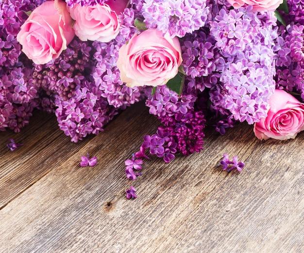 Fioletowe kwiaty bzu z różowymi różami na drewnianym stole