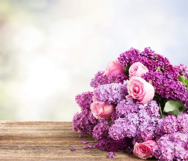 Fioletowe kwiaty bzu z różowymi różami z bliska na drewnianym stole, kopia przestrzeń na szarym bokeh