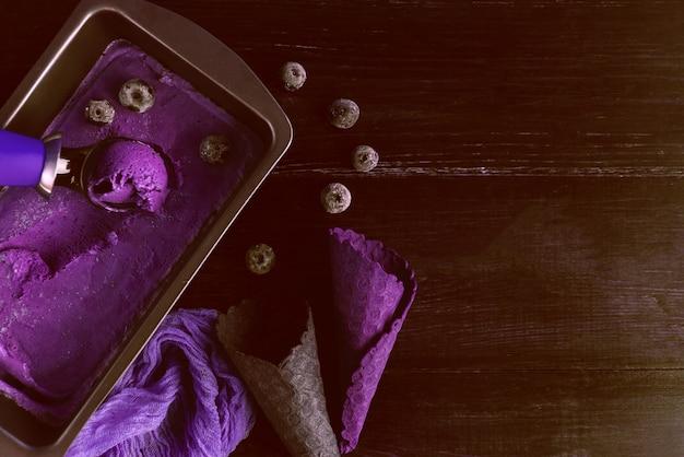Fioletowe lody z łopatką do lodów na ciemnym drewnianym tle z waflowymi filiżankami
