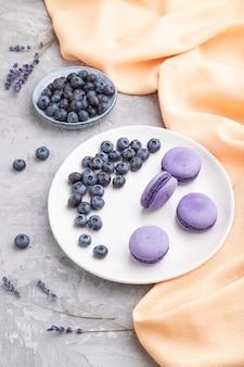 Fioletowe macarons lub macaroons cakes z jagodami na białym talerzu ceramicznym na szarej betonowej powierzchni i pomarańczowej tkaninie