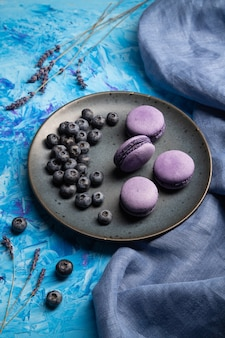 Fioletowe macarons lub macaroons cakes z jagodami na talerzu ceramicznym na niebieskim tle betonu i niebieskiej tkaninie.