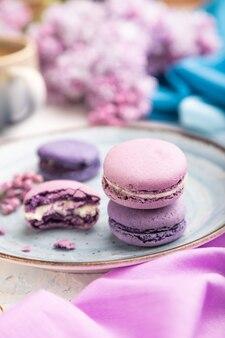 Fioletowe macarons lub macaroons z filiżanką kawy na białej betonowej powierzchni i magenta-niebieskiej tkaninie