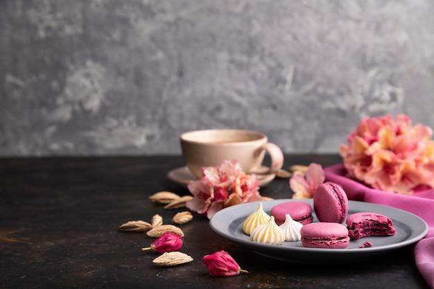 Fioletowe macarons lub macaroons z filiżanką kawy na czarnej betonowej powierzchni i różowej tkaninie