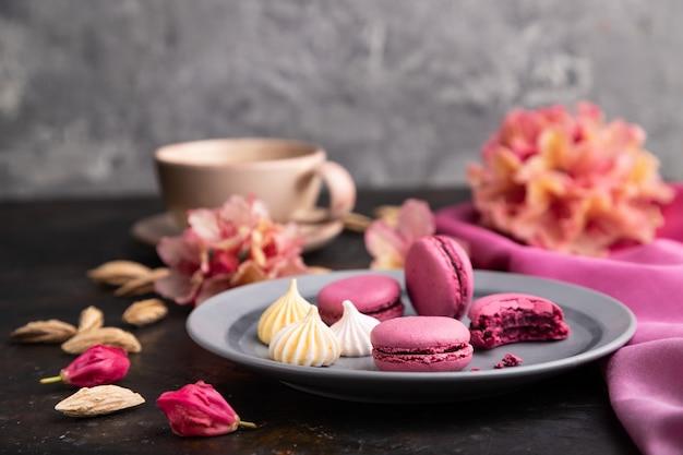 Fioletowe makaroniki lub ciasta makaronikowe z filiżanką kawy na czarnym betonowym tle i różowej tkaninie. widok z boku, z bliska,
