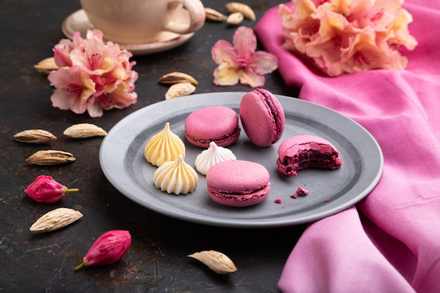 Fioletowe makaroniki lub ciasta makaronikowe z filiżanką kawy na czarnym betonowym tle i różowej tkaninie. widok z boku,