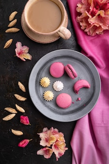 Fioletowe makaroniki lub ciasta makaronikowe z filiżanką kawy na czarnym betonowym tle i różowej tkaninie. widok z góry, płasko ułożony,