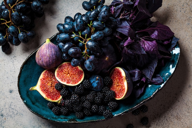 Fioletowe owoce i jagody w niebieskim naczyniu, szare tło. purpurowe tło żywności.