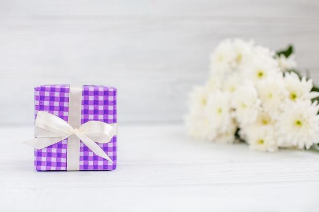 Fioletowe pudełko z prezentem i kwiatami. koncepcja dnia matki, urodziny, 8 marca.