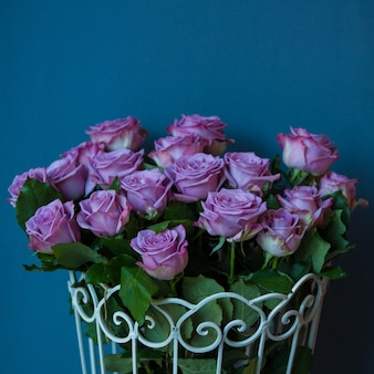 Fioletowe róże w metalicznym koszu w studio fotograficznym