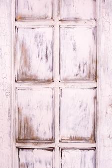 Fioletowe tło drewniane. różowe stare okno. drzwi retro. pęknięcia i zadrapania, rustykalne.