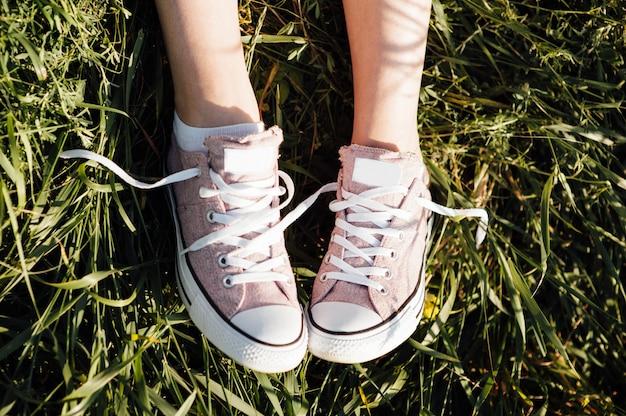 Fioletowe trampki na nogach dziewczyna na trawie