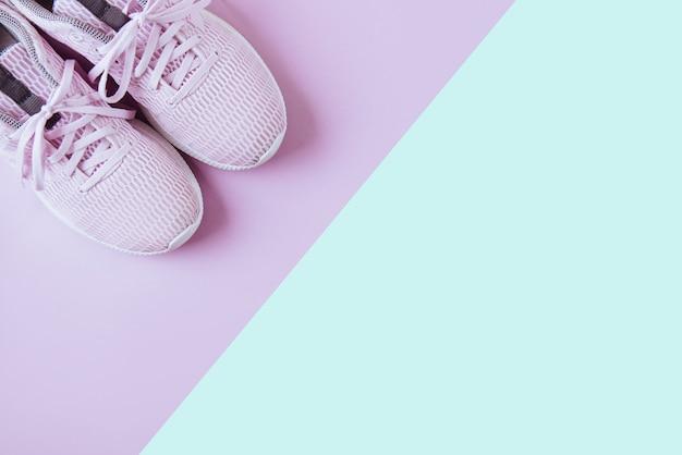 Fioletowe trampki, różowe i niebieskie tło.