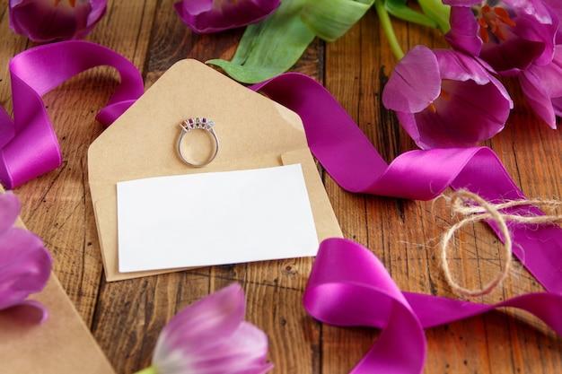Fioletowe tulipany, pierścień i pustą kartę na drewnianym stole z bliska