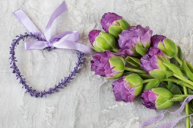 Fioletowe tulipany wiązane koronkową wstążką i fioletowym sercem obok