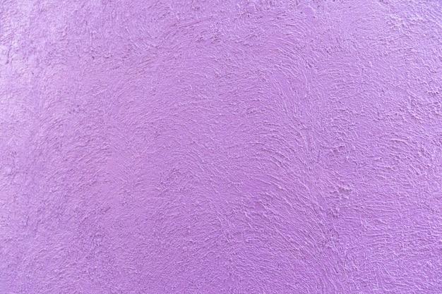 Fioletowo-fioletowy kolor na cementowej krzywej abstrakcyjnej losowej tekstury na ścianie w godzinach popołudniowych.