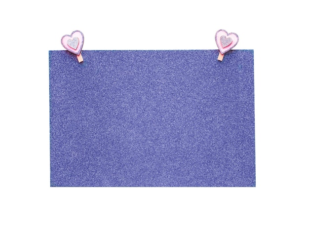 Fioletowy brokat arkusz papieru z różowymi spinaczami do bielizny w kształcie serca na białym tle