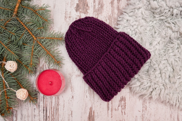 Fioletowy kapelusz. świerkowa gałąź, girlanda i świeca.
