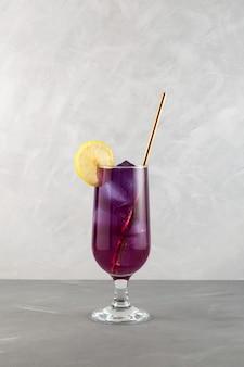 Fioletowy koktajl podany z cytryną i słomką do picia letni napój orzeźwiający