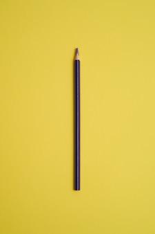 Fioletowy kolorowy ołówek na białym tle na żółty stół