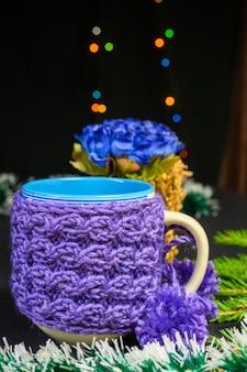 Fioletowy kubek z dzianiny z pomponami. boże narodzenie i nowy rok koncepcja na czarnym tle.