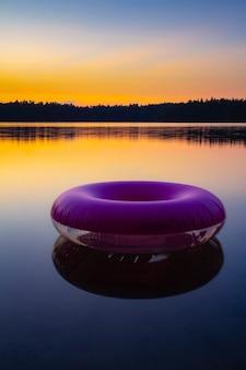Fioletowy nadmuchiwany pierścień do pływania na powierzchni nieruchomej wody jeziora o zachodzie słońca