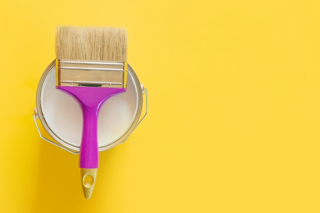 Fioletowy pędzel z otwartą puszką białej farby na żółtym,